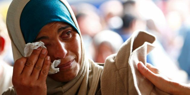 Syrian refugee Asmaa wipes tears as she waits for a train on the platform at the main railway station...