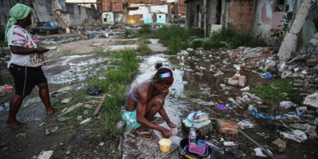 RIO DE JANEIRO, BRAZIL - JULY 24: Alessandra washes kitchen items with a small hose amidst the rubble...