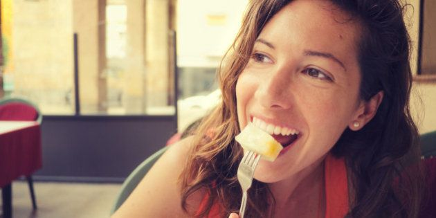 Natural portrait of pretty young woman eating seme fruit in an outdoor restaurant.