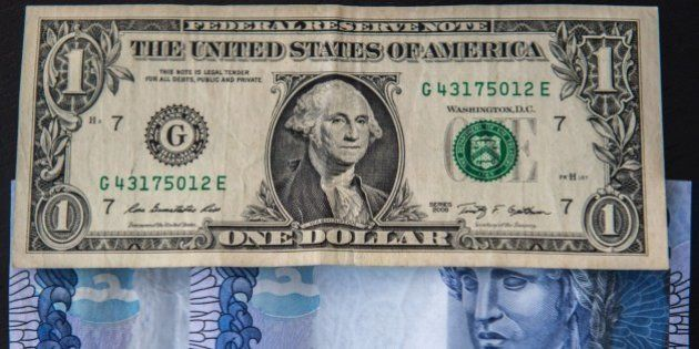Picture depicting US dollar notes and Brazilian reals at the exchange rate of one dollar bill per 4,...