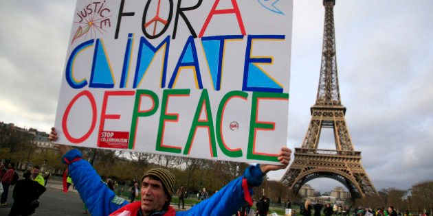 An activist hold a poster during a demonstration near the Eiffel Tower, in Paris, Saturday, Dec.12, 2015...