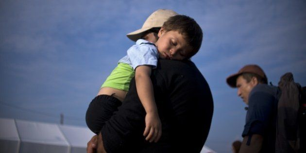 A migrant man holds his sleeping child as migrants and refugees queue to be registered at a camp after...