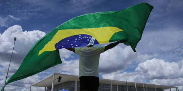 A man holds up a Brazilian national flag, also known as the Auriverde, in front of the Planalto presidential...