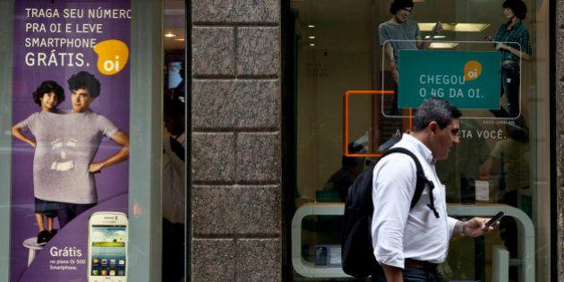 A customer exits an Oi SA retail store in Rio de Janeiro, Brazil, on Wednesday, Oct. 2, 2013. Oi SA,...