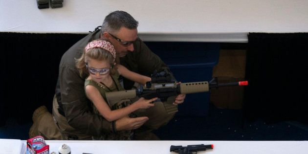 A man shows a girl how to hold an airsoft gun during the NRA Youth Day at the National Rifle Association's...