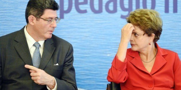 Brazilian President Dilma Rousseff (R) and her Finance Minister Joaquim Levy, talk during the signing...