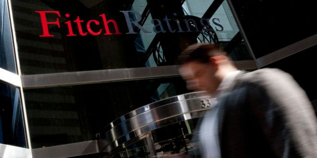 Pedestrians walk past the logo for Fitch Ratings Ltd. outiside their offices in New York, U.S., on Tuesday,...