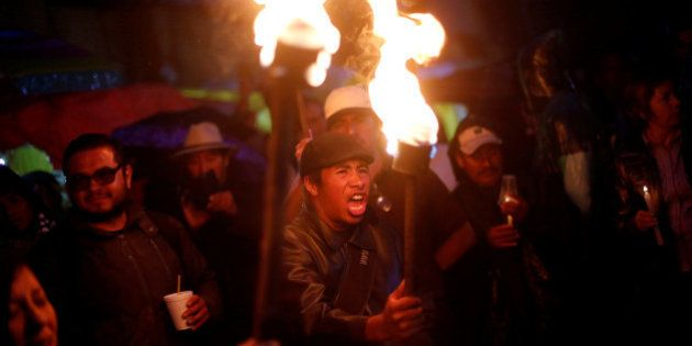A protester from the National Coordination of Education Workers (CNTE) teachers' union holds a torch...