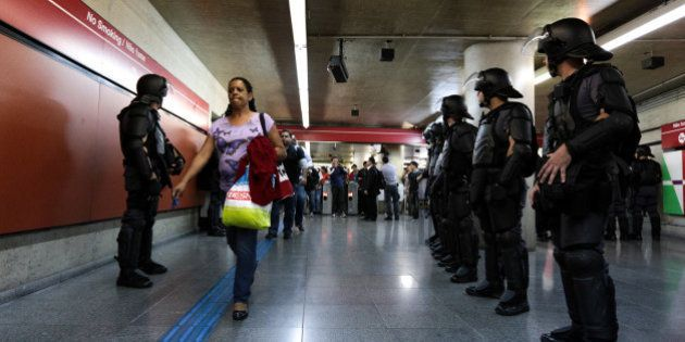 ROOSEVELT SQUARE, SAO PAULO, BRAZIL - 2014/07/01: A woman passes by riot policemans in the Anhangabaú...