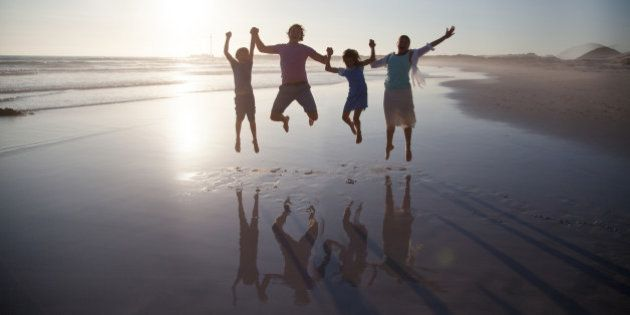Family with two children jumping together on a beach at