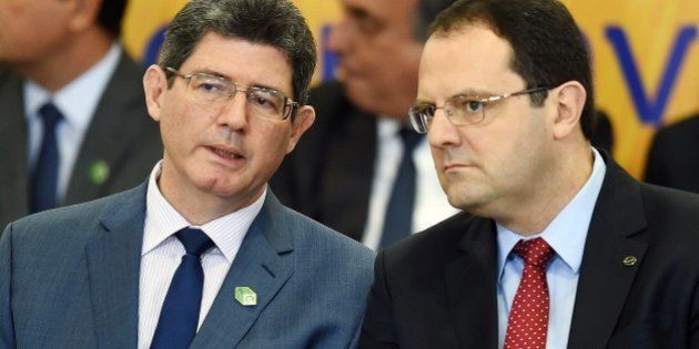 Brazilian Finance Minister Joaquim Levy (L) speaks with Planning Minister Nelson Barbosa during the launching...
