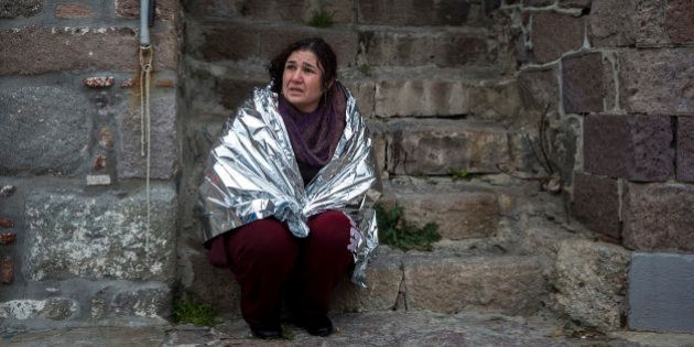 A woman wearing a thermal blanket reacts after being rescued, after the boat she and dozens of other...