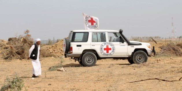 A man walks near an International Committee of the Red Cross (ICRC) vehicle as the comittee assists Palestinian...
