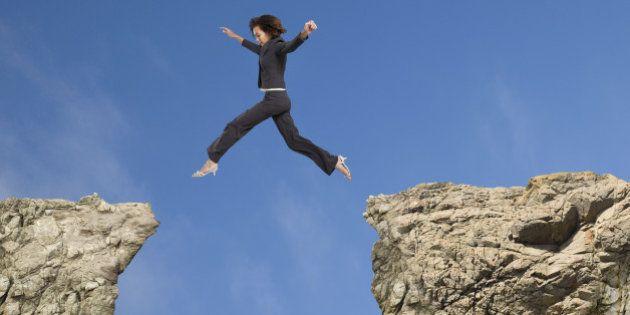 Mixed race businesswoman jumping over gap between