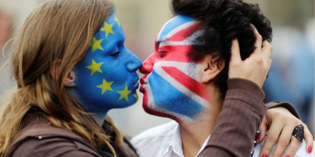 Two activists with the EU flag and Union Jack painted on their faces kiss each other in front of Brandenburg...