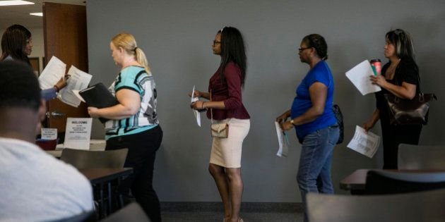 Job seekers wait in line to meet with representatives during a weekly job fair event in Dallas, Texas,...
