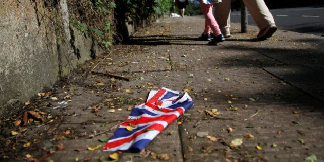 A British flag which was washed away by heavy rains the day before lies on the street in London, Britain,...