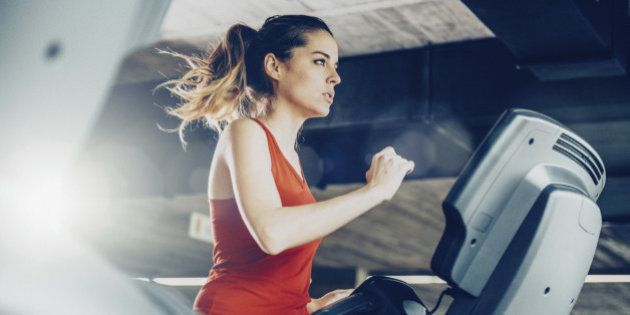 Healthy young woman in GYM running on