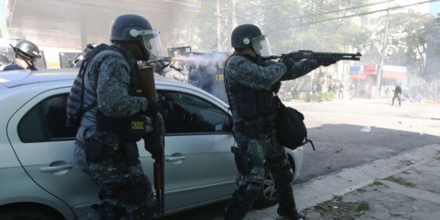 SAO PAULO, BRAZIL - JUNE 12: Police fire non-lethal rounds at protestors during a World Cup protest outside...