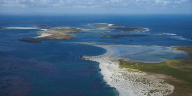 Beautiful white sandy beaches and clear blue waters of the Falkland Islands in the South