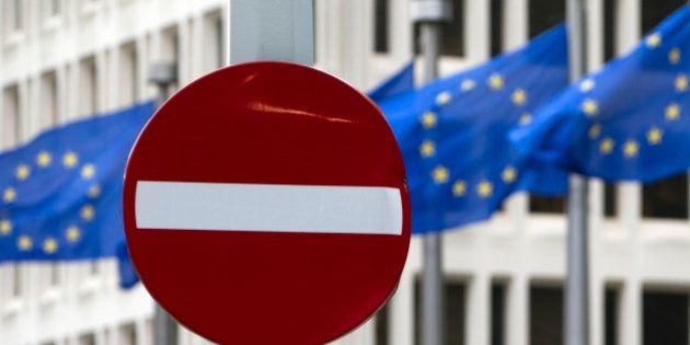 EU flags flutter in the wind in back of a no entry street sign in front of EU headquarters in Brussels...