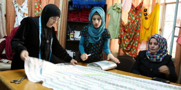 In this Tuesday, Feb. 16, 2016 photo, Jordanian volunteer Dunya Shawaqfeh, 59, teaches sewing to Jordanian...