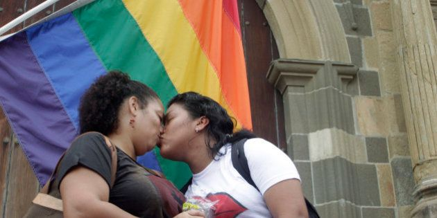 Valentina (L) and Johanna kiss while standing outside the Metropolitan Cathedral in Panama City May 29,...
