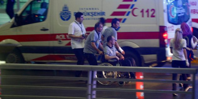 Paramedics help a man in a wheelchair at Turkey's largest airport, Istanbul Ataturk, Turkey, following...