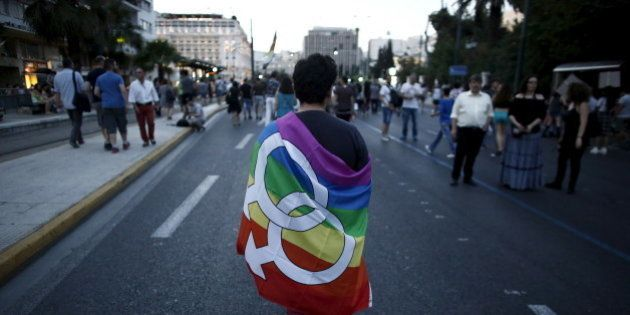 A gay rights activist wearing a rainbow flag walks through the city centre during a Gay Pride parade in Athens, June 13, 2015. REUTERS/Kostas Tsironis