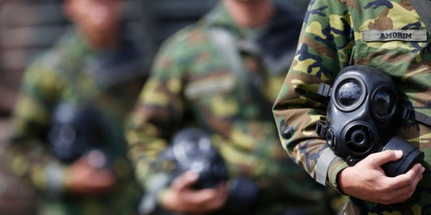 A soldier holds a gas mask during a event by members of the Brazilian Army, Navy and Air Force presenting...