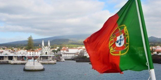 The Portuguese flag flaps above a ferry leaving Madalena on Pico Island,