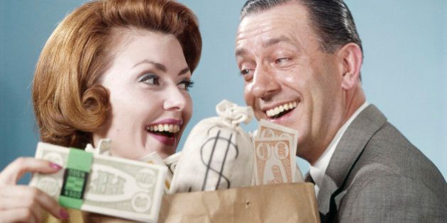 1960s HAPPY COUPLE MAN WOMAN HOLDING SHOPPING BAG FULL OF MONEY LAUGHING LOOKING AT EACH OTHER (Photo...