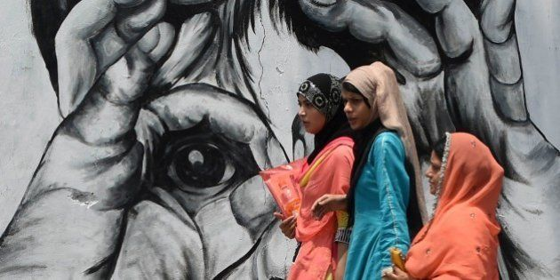 Pakistani women walk past a mural painted along a street in Lahore on June 15, 2015. AFP PHOTO / ARIF...