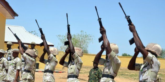 Nigerian soldiers shoot into the air during a ceremony to mark the release of suspected detainees cleared...
