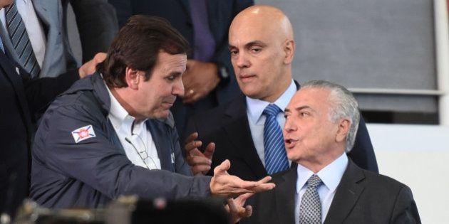 Rio de Janeiro's Mayor Eduardo Paes (L) speaks with Brazilian acting Michel Temer (R) during a visit...