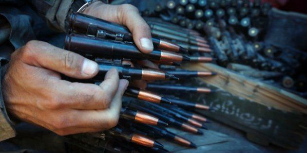 An Iraqi Kurdish Peshmerga fighter prepares an ammunition belt as he guards a position at the frontline...