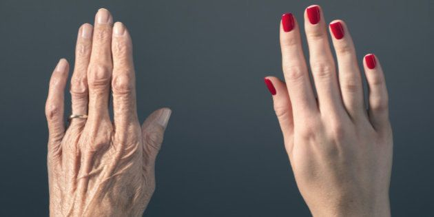 Studio photograph of elderly woman's hand beside a younger woman's