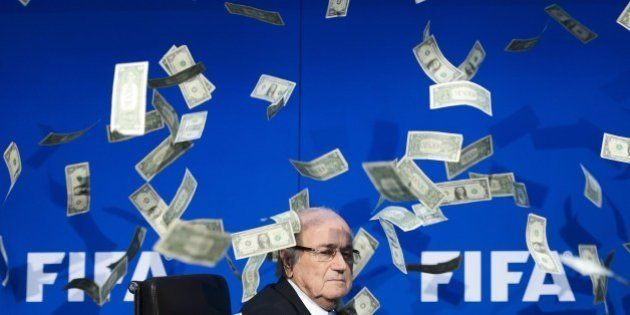 FIFA president Sepp Blatter looks on as fake dollar notes fly around him, thrown by a British comedian...