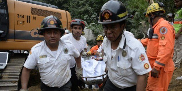 Volunteer firemen carry a body recovered from the mud and debris after a landslide late Thursday, following...