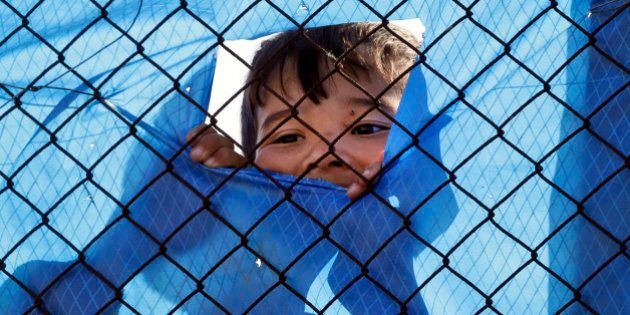A migrant child looks out behind a wire fence of a refugee camp in the western Athens' suburb of Schisto,...