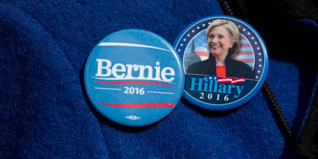 A demonstrator wears Democratic presidential candidate's Sen. Bernie Sanders, I-Vt., and Hillary Clinton...