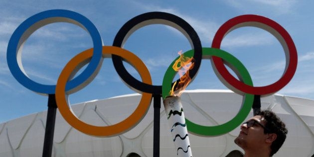 Brazilian designer Glauber Penha takes part in the Olympic Flame torch relay in front of the Arena da...