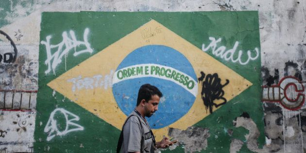 RIO DE JANEIRO, BRAZIL - SEPTEMBER 23: A man walks in front of a painted Brazilian flag and other graffiti...