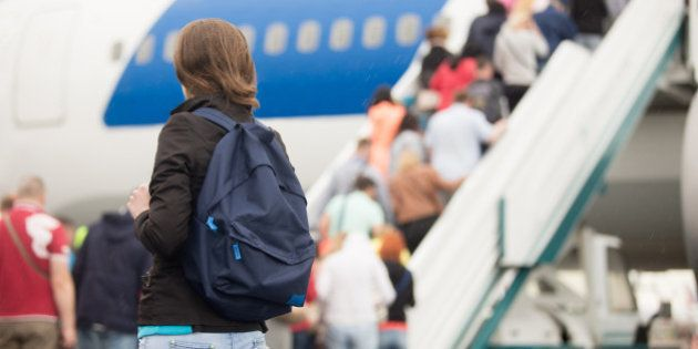 Young woman passenger in 20s travelling with backpack, boarding airplane, people climbing ramp on background,...