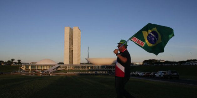 An anti-government protestor carries a Brazilian flag with the message in