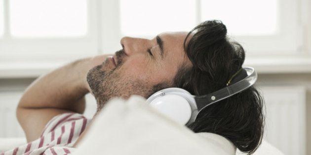 Germany, Berlin, Mature man listening music with head