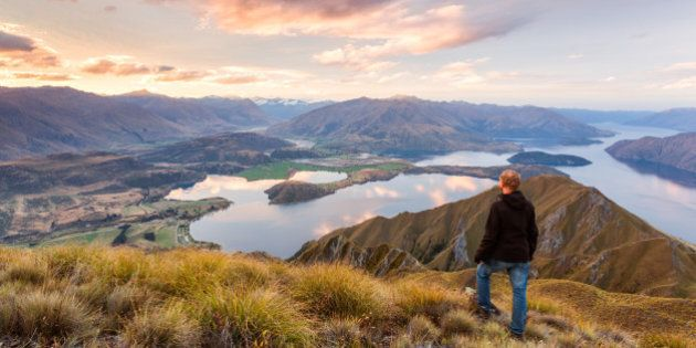 Tourist looking at Wanaka lake and Southern Alps from the top of Mt Roy at sunset, Wanaka, Otago region,...