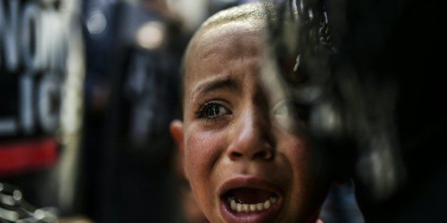 A boy cries during a protest held by migrants and refugees to call for the reopening of the borders at...
