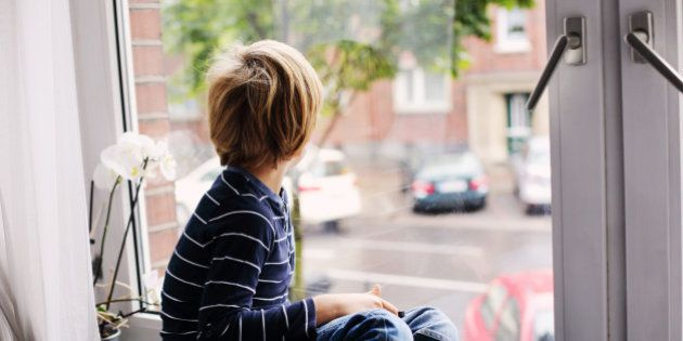 7 year old boy sitting near the window and playing