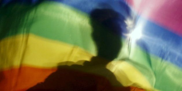 A gay man is silhoutted on a gay rainbow flag during a demonstration for gay rights in Hanoi, Vietnam,...